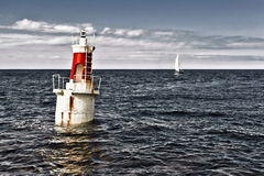 The lighthouse and the sail. A sail is coming back to the port in San Vicente, Spain Royalty Free Stock Images