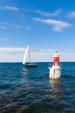 The lighthouse and the sail. A sail is coming back to the port in San Vicente, Spain Royalty Free Stock Photo