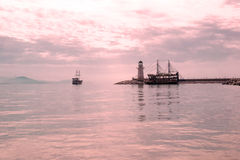 Lighthouse and sail ships in the Mediterranean sea at sunset Royalty Free Stock Image