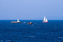 Lighthouse and sailboat Stock Images