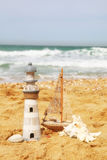 Lighthouse, sailboat on sea sand and ocean horizon. Royalty Free Stock Image