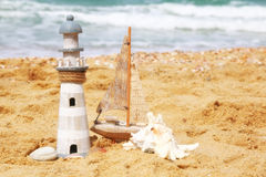 Lighthouse, sailboat on sea sand and ocean horizon. Stock Photography