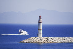Lighthouse and sailing Boat Royalty Free Stock Photos