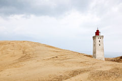 Lighthouse and sand dune. Rolling sand dune landscape and a lighthouse Royalty Free Stock Image