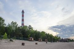 Lighthouse on the sandy beach of the lake in the evening royalty free stock photos