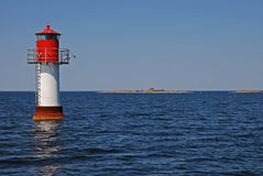 Lighthouse in the sea Stock Images