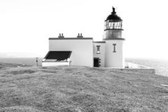 Lighthouse with sea in black and white. Small Stoer Head lighthouse with keepers house and bright sea in the background, in black and white stock image