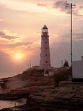 Lighthouse at sea coastline. Sunset on beach. Tined toned colora. Tion image with color filters Royalty Free Stock Photo