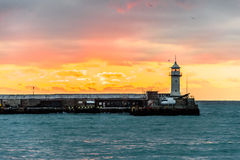 Lighthouse on the sea at the dawn. Royalty Free Stock Image