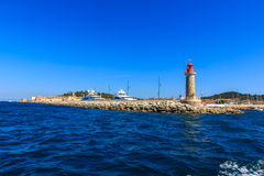 Lighthouse at the sea port of Saint - Tropez, Cote. Lighthouse and luxury yachts in sea port of Saint-Tropez, Cote dAzur, France - view from the Bay of Saint stock photography