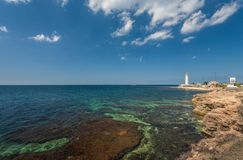 Lighthouse, sea and rock, blue sky Stock Images