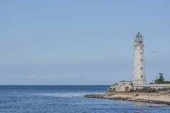Lighthouse, sea and rock, blue sky Stock Image