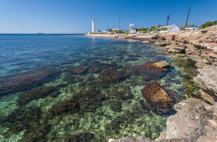 Lighthouse, sea and rock, blue sky. Crimea. Stock Photos