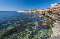 Lighthouse, sea and rock, blue sky. Crimea. Royalty Free Stock Photo