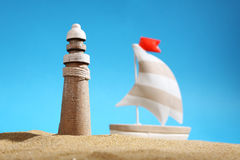 Lighthouse on sea sand, sailboat and blue sky Stock Images