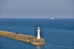 Lighthouse on sea with ship Stock Image