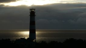 Lighthouse on the sea under stormy clouds and with the ship in the background