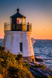 Lighthouse and Seagull at Sunset. Seagull flies past lighthouse at sunset on Newport RI coast near Castle Hill Inn Stock Photo