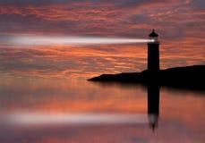 Lighthouse searchlight beam through marine air at night.
