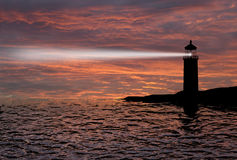 Lighthouse searchlight beam through marine air at night. Stock Photo