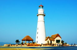 Lighthouse in seashore. Lighthouse and small thatched-roofed hut in seashore Royalty Free Stock Photos