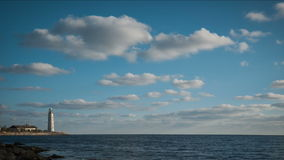 Lighthouse on the seashore under clouds. stock footage