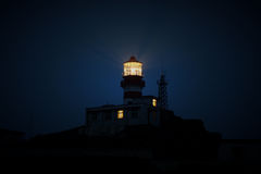 Lighthouse shining at night Stock Photo