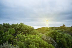 Lighthouse shining protective light over ocean Royalty Free Stock Images