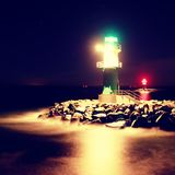 The lighthouse shinning at port gate. Modern light house at the end of stony pier Royalty Free Stock Photography