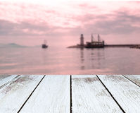 Lighthouse and ships, the sea, sunset, wooden plank in perspective Stock Image
