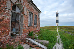Lighthouse on the shore, North Russia. Lighthouse on the shore next to the ruined building in the north of Russia Stock Photo