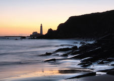 Lighthouse on shore at sunset. Scenic view of lighthouse, rocky shoreline and beach at sunset, Saint Mary's lighthouse, Whitley Bay, England stock photo