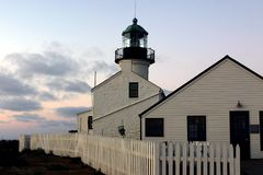 Lighthouse side view. A lighthouse with a white picket fence Royalty Free Stock Photography