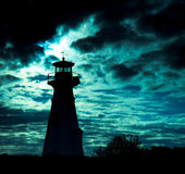 Lighthouse silhouette against ominous sky. Stock Photography