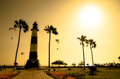 Lighthouse silhouette among golden sunset sea Royalty Free Stock Photography