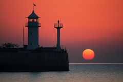 Lighthouse. Silhouette of a lighthouse in morning sunrise Stock Photo