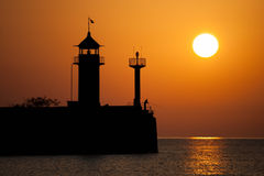 Lighthouse. Silueet of a lighthouse and silueet fisherman in morning sunrise Royalty Free Stock Photos