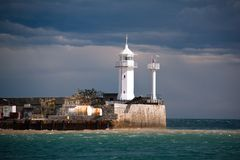 Lighthouse sits on the edge of the black sea. View of sky and sea few minutes before storm royalty free stock image
