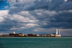 Lighthouse sits on the edge of the black sea. View of sky and sea few minutes before storm stock photos