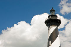 Lighthouse, sky and clouds. A view of a tall, black and white lighthouse against a blue sky with puffy white clouds in the background Royalty Free Stock Photos