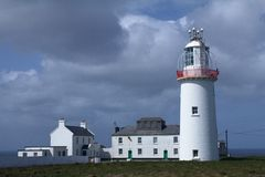 Lighthouse and sky on the irish coast Royalty Free Stock Photography