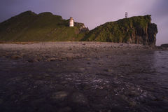 Lighthouse on the slope of the cape. Royalty Free Stock Image