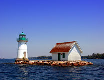 Lighthouse on the St Lawrence River in New York. Lighthouse and cabin atop a tiny rock island on the St Lawrence River in New York State Stock Image