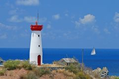 Lighthouse in St. Marten. White and red lighthouse on hill top in St. Marten West Indies overlooking ocean with sailboat in background stock photos