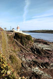 Lighthouse with stairs to rocky beach. Lighthouse during a sunny day on the rocks in with steps to beach in youghal county cork ireland Stock Photo