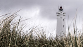 A lighthouse standing in a field of thick grass. A white clean modern lighthouse on the west coast of Denmark stand against a cloudy sky. A beautiful pattern of Stock Image