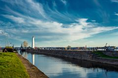 The lighthouse stands on the beach and canal, the blue sky with clouds and reflection in the water.  Stock Photo