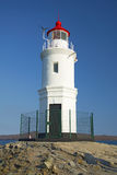 A lighthouse stands on a raised platform in the middle of the sea. Lighthouse in the sunshine Stock Images