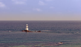 Lighthouse on the stone and sea Stock Images