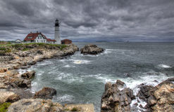 Lighthouse on Stormy Day. A lighthouse at the end of a rocky shore on a stormy day Stock Photos
